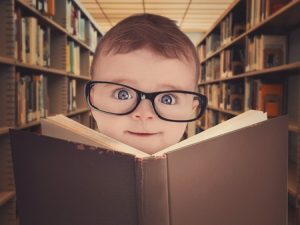 36536917 - a cute little baby is wearing eye glasses and reading a library book for an education or learning concept.